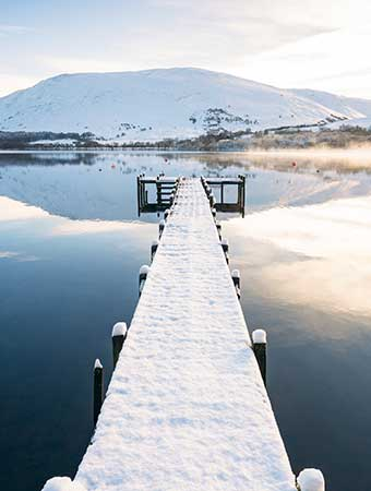 Snow covered jetty leading to a lake with snow covered mountains behind
