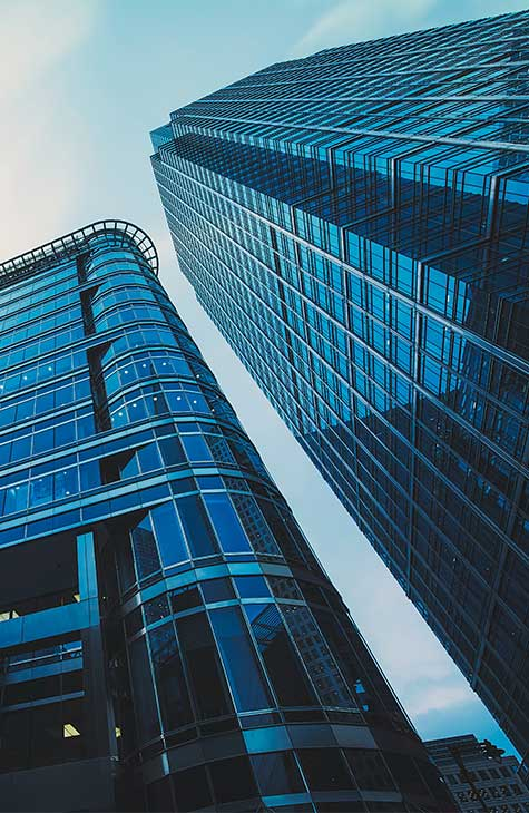 Two glass skyscrapers pictured from the ground looking up