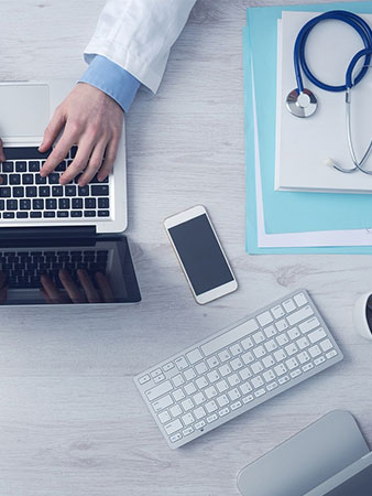 A doctors desk showing a laptop, keyboard and iPhone alonmg with a blue stethoscope