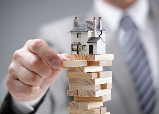 A suited man removing a jenga stly eblock from a tower with a house atop of it